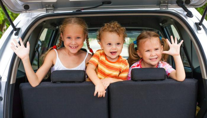 3 happy kids in car